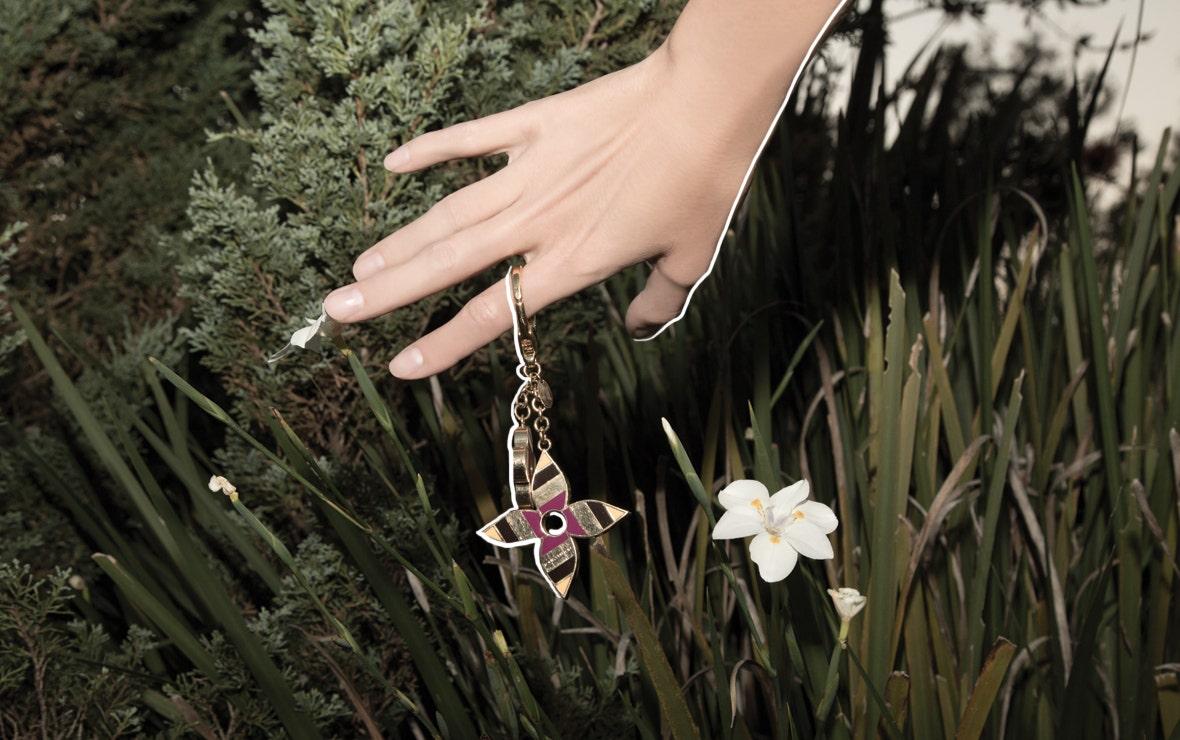 Mano de mujer con llavero sobre arbusto en paisaje natural