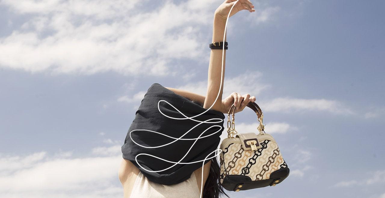 Mujer con blusa negra cubriendo su rostro sujetando un bolso de mano color beige