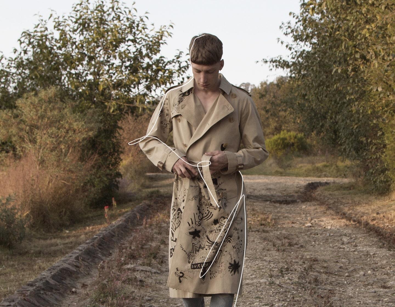 Hombre con gabardina en paisaje natural